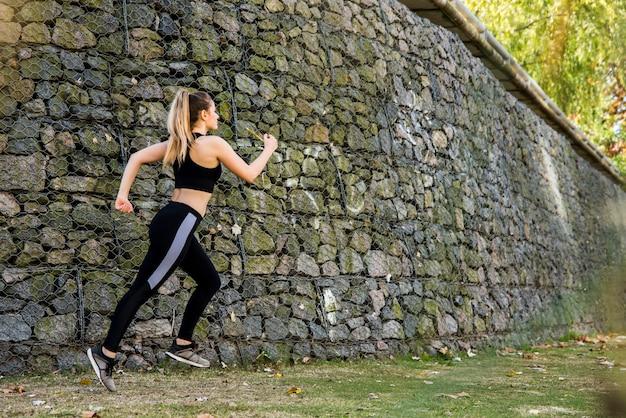 Jeune femme qui court à l'extérieur avec des vêtements de sport Photo gratuit