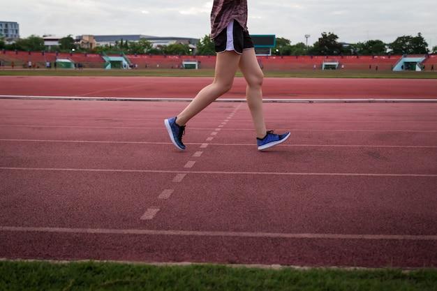 Jeune femme qui court sur la piste du stade. Photo Premium