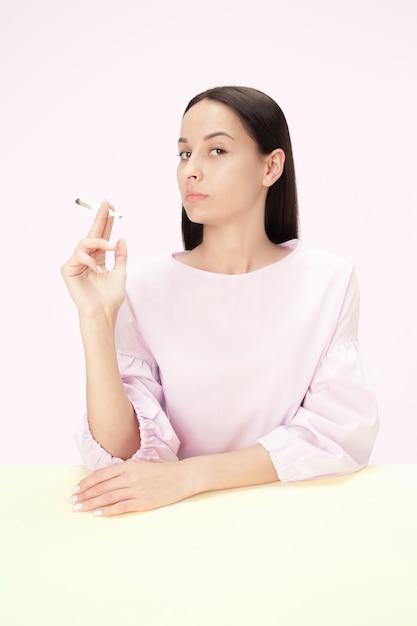 La Jeune Femme Qui Fume Une Cigarette Assise à Table Au Studio. Photo gratuit