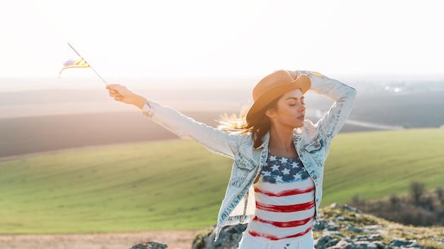 Jeune femme qui pose en t-shirt drapeau américain au sommet de la montagne Photo gratuit