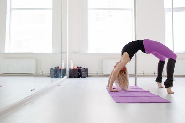 Jeune femme qui s'étend ses jambes après la séance d'entraînement concept yoga et pilates Photo Premium