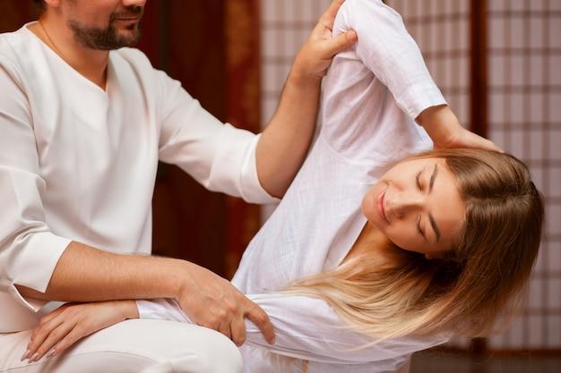 Jeune femme qui s'étend de son corps avec l'aide d'un thérapeute de massage thaïlandais professionnel au centre de bien-être. masseur masculin effectuant un massage thaïlandais sur son client. loisirs, détente, guérison Photo Premium