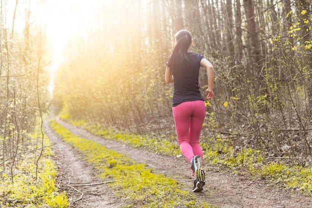 Jeune femme qui traverse la forêt Photo gratuit