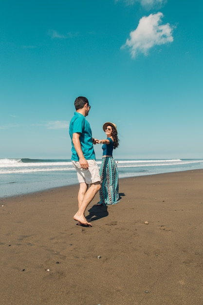 Jeune femme qui veut son homme suivre au bord de l'eau sur la plage Photo gratuit