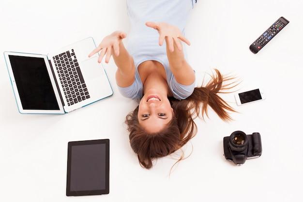 Jeune femme de race blanche avec des appareils électroniques Photo gratuit