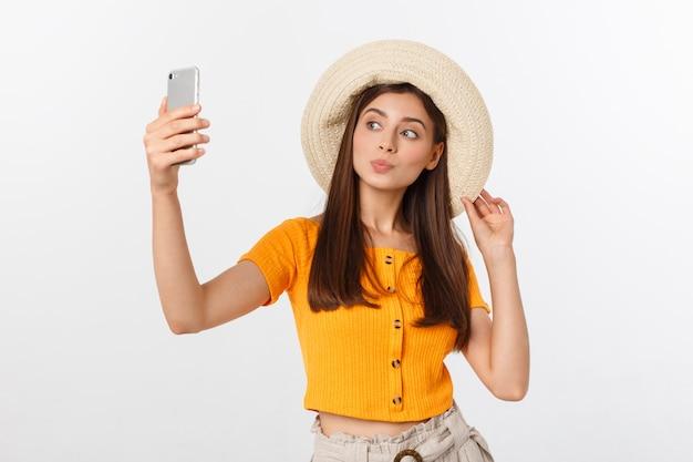 Jeune Femme De Race Blanche Appréciant Le Selfie Avec Elle-même Isolé Sur Le Concept De Voyage D'été Blanc. Photo Premium