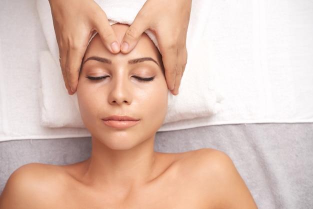 Jeune femme de race blanche ayant un massage facial anti-âge Photo gratuit