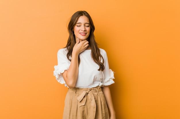 Une jeune femme de race blanche souffre de douleurs à la gorge causées par un virus ou une infection. Photo Premium