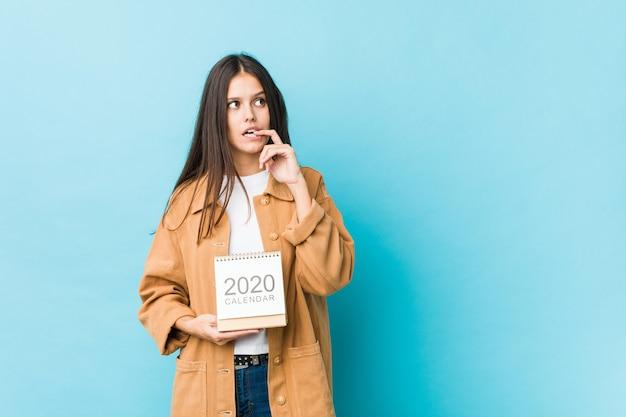 Jeune Femme De Race Blanche Tenant Un Calendrier Des Années 2020 Détendu Penser à Quelque Chose En Regardant Un Espace De Copie. Photo Premium