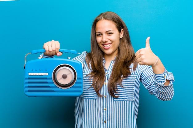 Jeune femme avec une radio vintage sur fond bleu Photo Premium