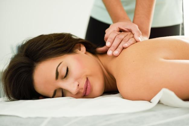 Jeune femme recevant un massage du dos dans un centre de spa. Photo gratuit