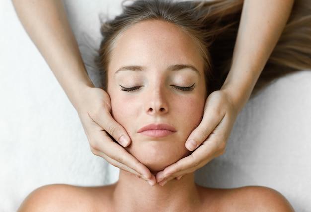 Jeune femme recevant un massage de tête dans un centre de spa. Photo gratuit