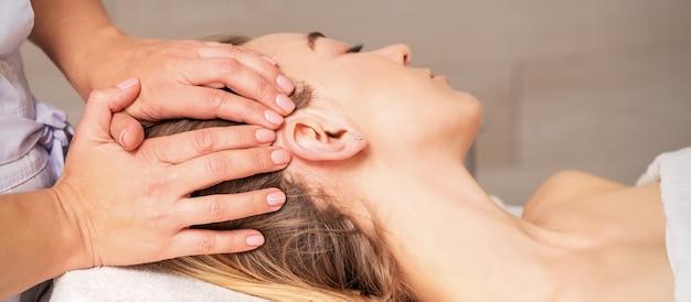 Jeune Femme Recevant Un Massage De La Tête Par Les Mains De L'esthéticienne Au Centre De Beauté Spa Photo Premium