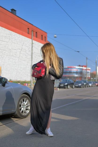 Jeune femme à la recherche d'une clé de sa voiture dans le sac Photo Premium
