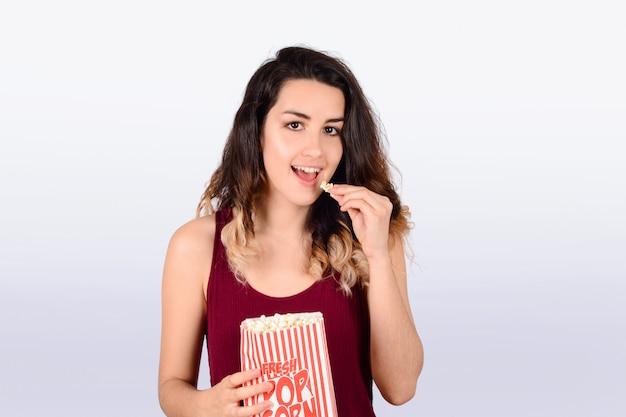 Jeune femme regardant manger du pop-corn. Photo Premium