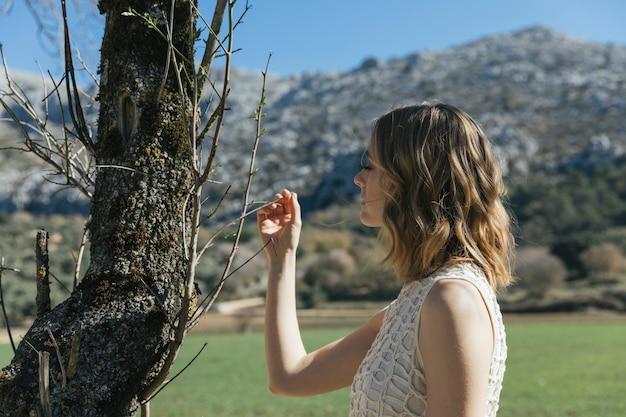 Jeune femme regardant de petites branches Photo gratuit