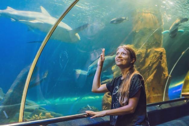Jeune Femme Regardant Des Poissons Dans Un Aquarium Tunnel Photo Premium