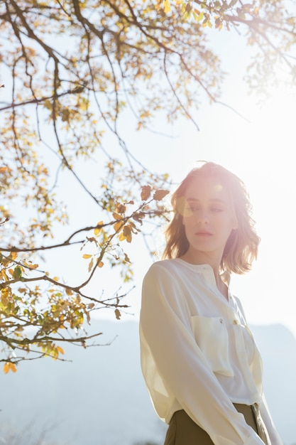Jeune femme regardant sous le soleil Photo gratuit
