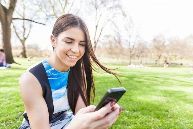 Jeune femme regardant un téléphone intelligent au parc de londres Photo Premium