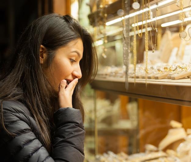 Jeune femme regardant la vitrine d'un bijou d'extérieur Photo Premium