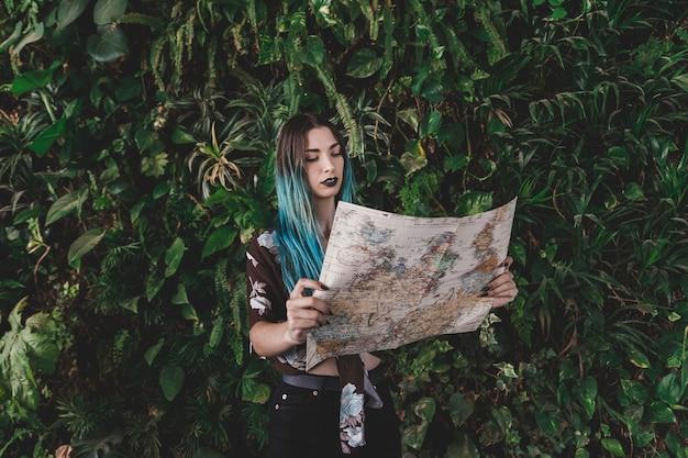 Jeune femme, regarder, carte vintage, debout, devant, plante Photo gratuit