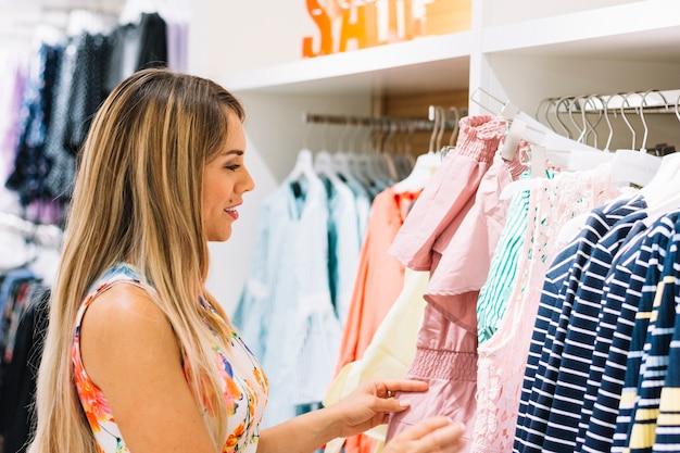 Jeune femme, regarder, vêtements, sur, rack, à, salle d'exposition Photo gratuit