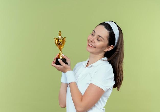 Jeune Femme De Remise En Forme En Bandeau Tenant Son Trophée En Le Regardant En Souriant Avec Un Visage Heureux Debout Sur Un Mur Léger Photo gratuit