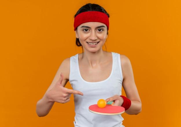 Jeune Femme De Remise En Forme En Tenue De Sport Avec Bandeau Tenant La Raquette Et La Balle Pour Le Tennis De Table Photo gratuit