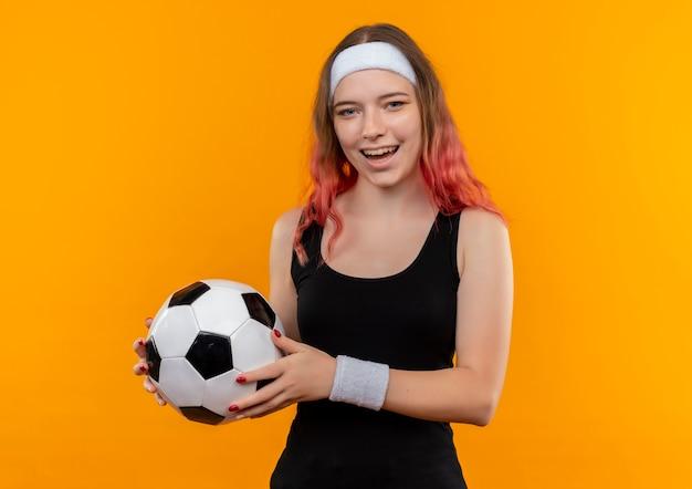 Jeune Femme De Remise En Forme En Tenue De Sport Tenant Un Ballon De Football Avec Un Visage Heureux Souriant Joyeusement Debout Sur Un Mur Orange Photo gratuit