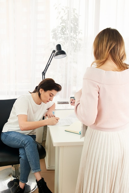 Jeune Femme Remplissant Et Signant Le Formulaire à Une Table Photo Premium