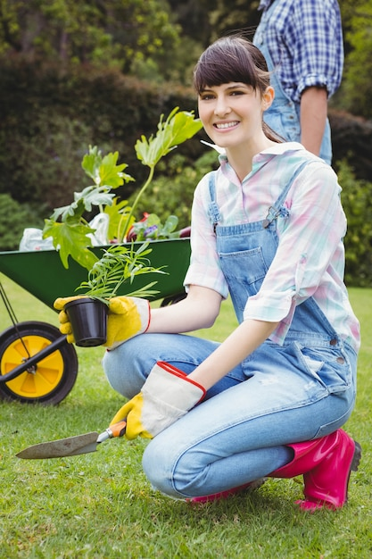 Jeune femme, rempotage, a, plante, dans jardin Photo Premium