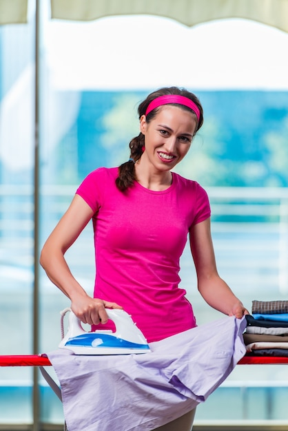 Jeune femme repassant des vêtements à bord Photo Premium