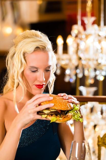 Jeune femme restaurant raffiné manger un hamburger, elle se comporte mal Photo Premium