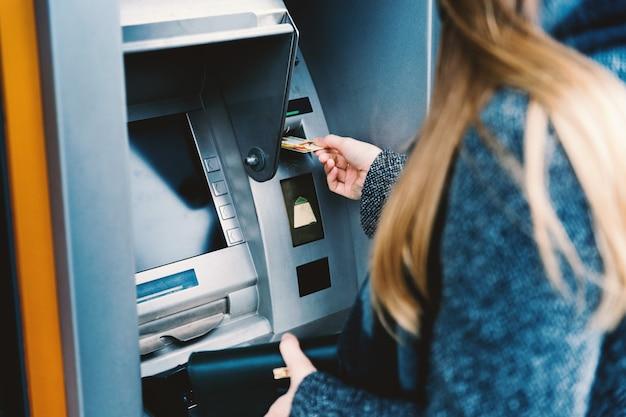 Jeune femme retirant de l'argent de la carte de crédit à l'atm Photo Premium