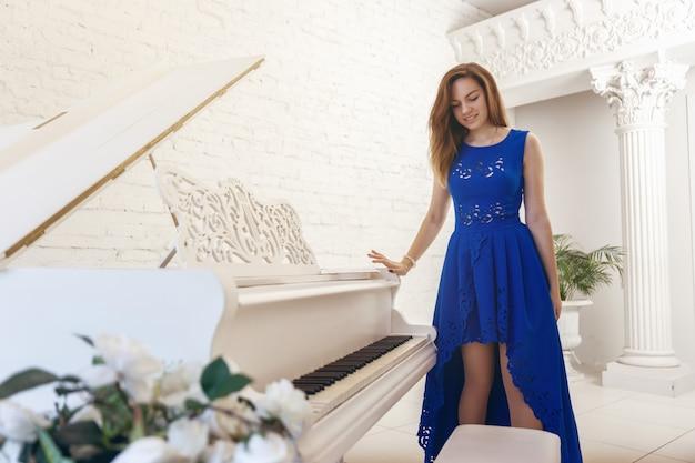 Jeune femme en robe bleue est debout près d'un piano blanc et baisse les yeux Photo Premium