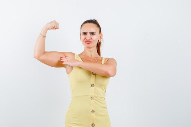 Jeune Femme En Robe Jaune Montrant Les Muscles Du Bras Et L'air Confiant, Vue De Face. Photo gratuit