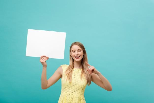 Jeune femme en robe jaune pointant le doigt au tableau blanc blanc de côté. Photo Premium