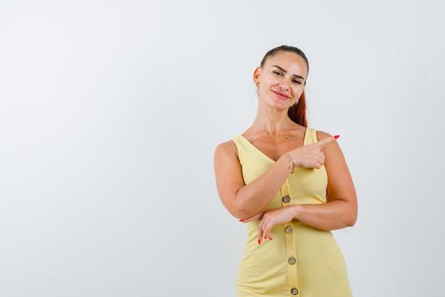 Jeune Femme En Robe Jaune Pointant Vers Le Coin Supérieur Droit Et à La Joyeuse Vue De Face. Photo gratuit