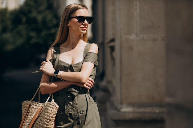 Jeune femme en robe verte debout près du vieux bâtiment Photo gratuit