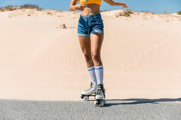 Jeune femme en rollers au bord de la route Photo gratuit
