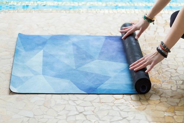 Jeune femme roulant son tapis de yoga bleu après un cours de yoga sur le sol près d'une piscine Photo Premium