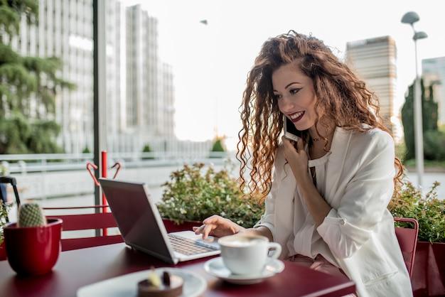 Jeune Femme Rousse D'affaires Sur L'ordinateur Et Le Téléphone Mobile Photo Premium