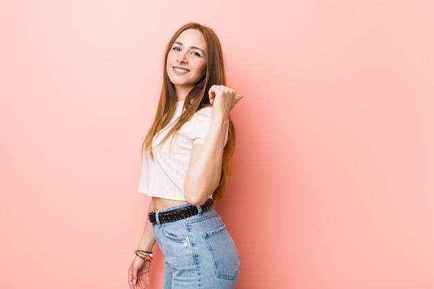Jeune Femme Rousse Au Gingembre Contre Un Mur Rose Pointe Avec Le Doigt Du Pouce Loin, Riant Et Insouciant. Photo Premium