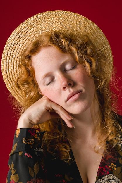 Jeune femme rousse aux yeux fermés, tenant le menton Photo gratuit