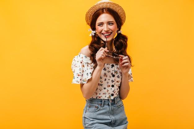 Jeune Femme Rousse De Bonne Humeur Sourit Et Tient Des Lunettes. Dame Au Chapeau De Paille Et Chemise à Imprimé Floral En Détournant Les Yeux. Photo gratuit