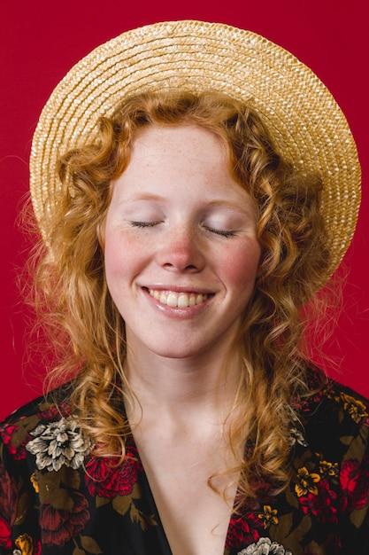 Jeune femme rousse a fermé les yeux et souriant Photo gratuit