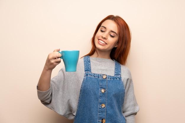 Jeune femme rousse sur isolé tenant une tasse de café Photo Premium