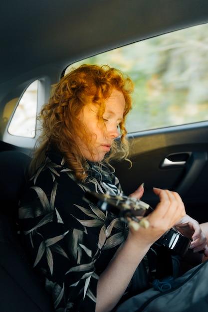 Jeune femme rousse jouant de la guitare en voiture Photo gratuit