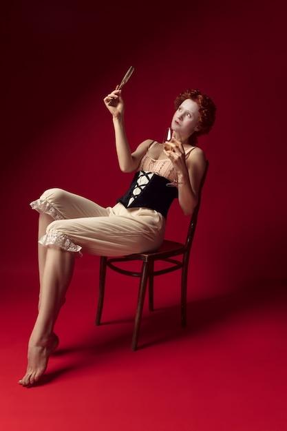 Jeune Femme Rousse Médiévale Comme Une Duchesse En Corset Noir Et Vêtements De Nuit Assis Sur Le Rouge Photo gratuit