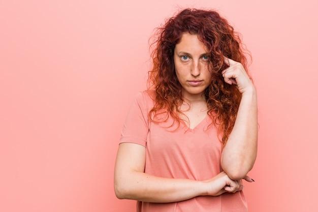 Jeune femme rousse naturelle et authentique pointant le temple avec le doigt, pensant, concentrée sur une tâche. Photo Premium